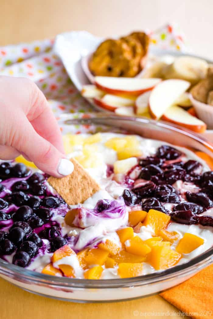 Dipping graham cracker in Greek Yogurt Cheesecake Fruit Dip topped with four kinds of fruit