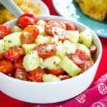 A bowl of Tomato Cucumber Salad with Feta Cheese on a red napkin
