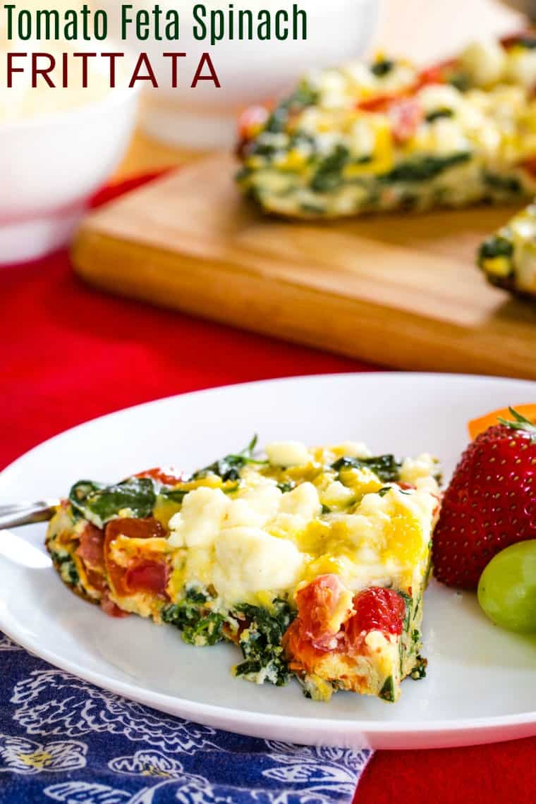 Tomato Feta Spinach Frittata is a baked eggs recipe being served on a white plate for breakfast or brunch