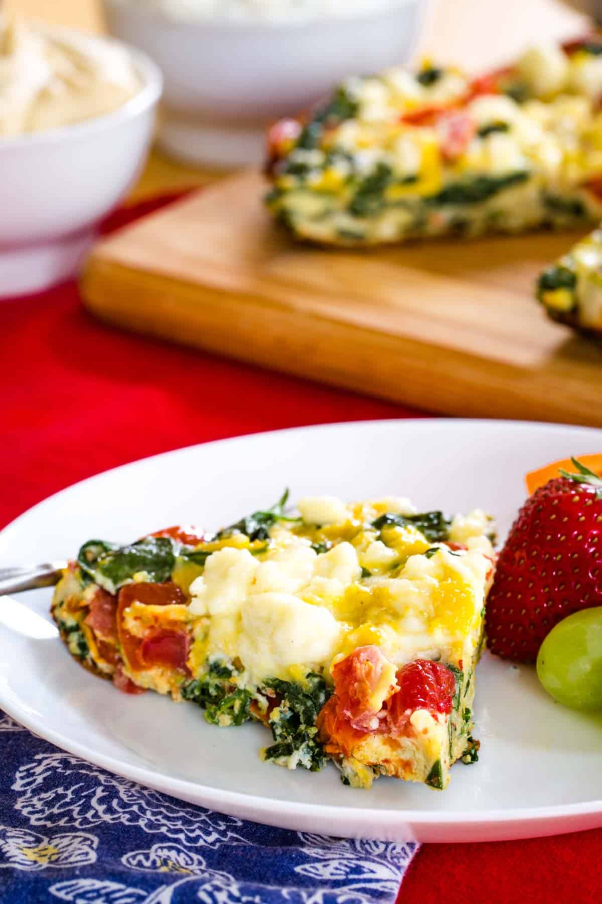 A piece of Spinach Tomato Feta Frittata on a white plate