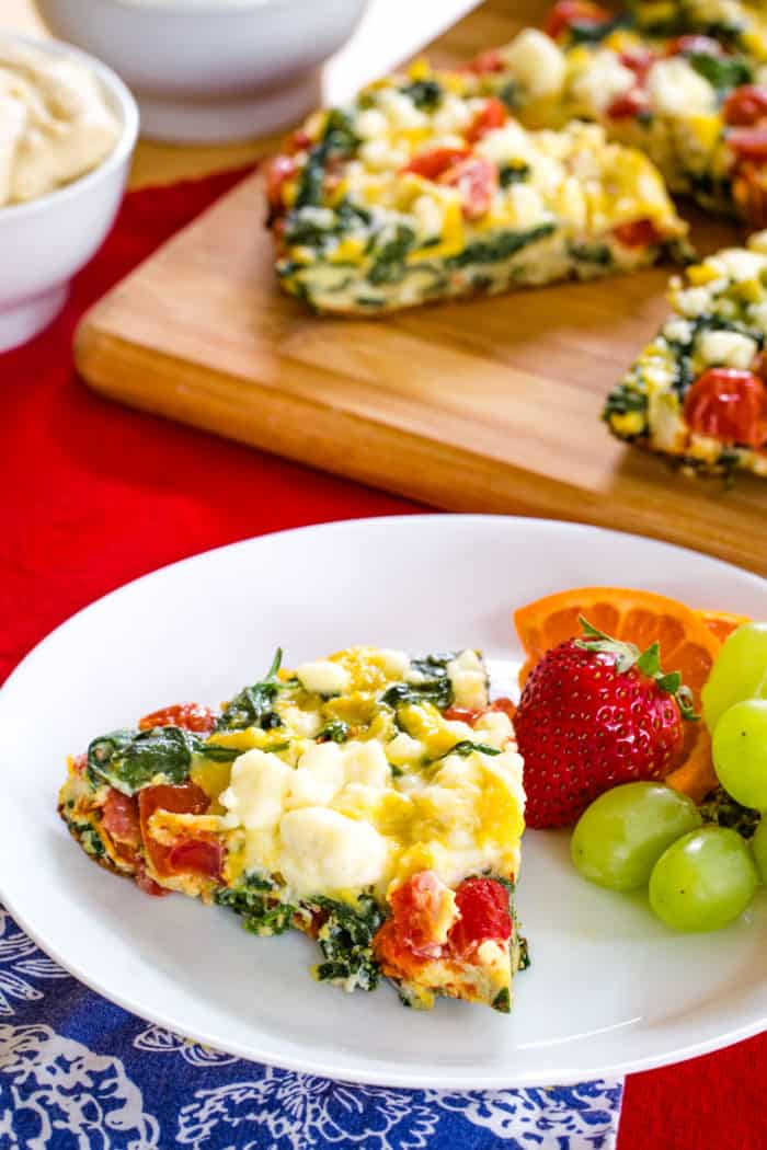 A slice of Spinach Tomato Feta Frittata served on a white plate with fruit