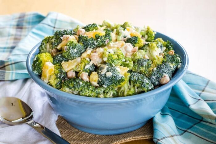 Tropical Pineapple Broccoli Salad in a blue serving bowl with a spoon