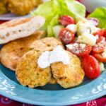 Easy gluten free falafel on a blue plate with tomato cucumber feta salad