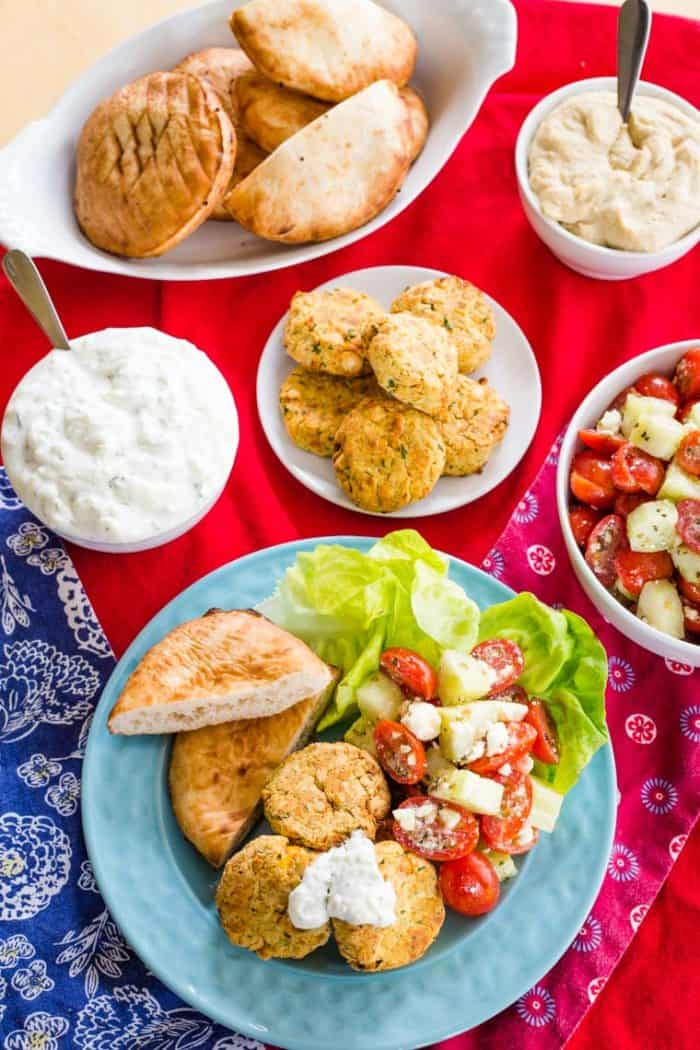 Overhead of a Mediterranean dinner with falafel, pita, hummus, tomato cucumber salad, and tzatziki
