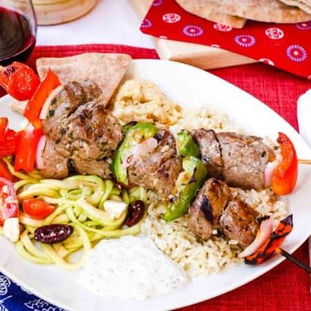 Greek Beef Kabobs with tzatziki, pita, rice, and zoodles Greek salad