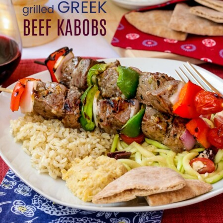 Greek Beef Kabobs on the grill served with rice and hummus and pita