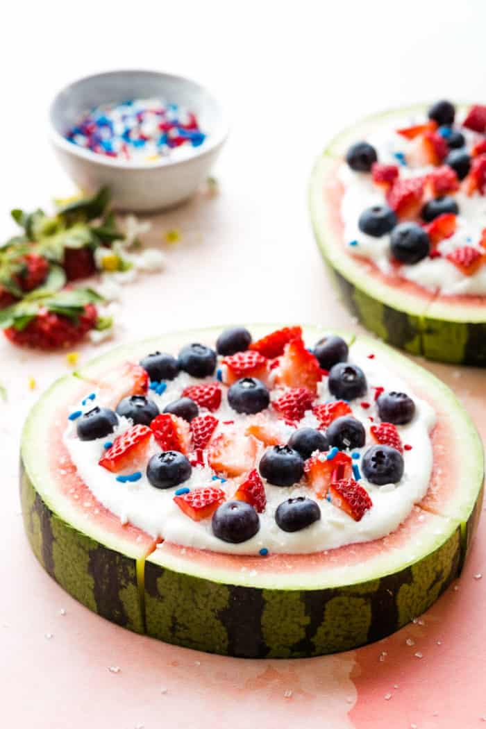 A round of watermelon topped with whipped cream, berries, and sprinkles and sliced like a pizza
