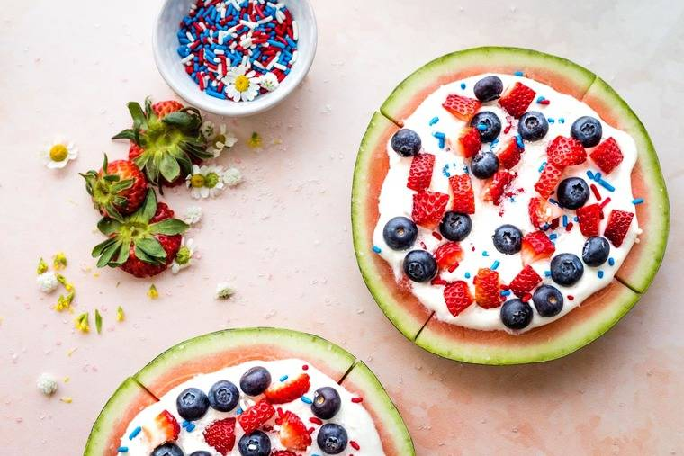 Overhead shot of two watermelon fruit pizzas topped with yogurt and berries plus a bowl of sprinkles