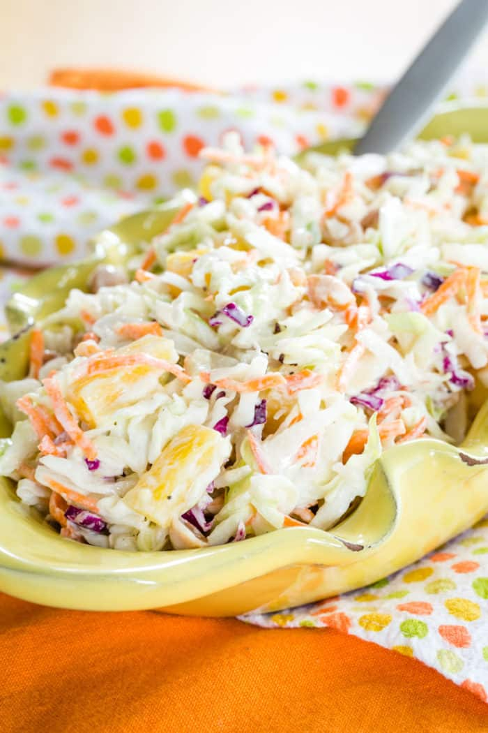 Healthy Tropical Coleslaw in a yellow bowl on an orange napkin