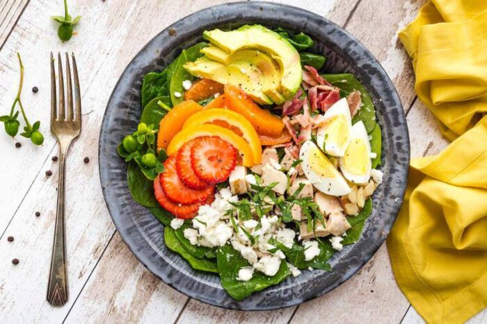 Strawberry Avocado Spinach Salad on a tin plate with antique fork and mustard-colored napkin