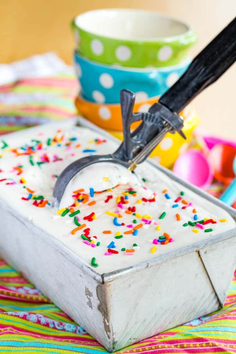 A scoop in a container of Cake Batter No-Churn Ice Cream