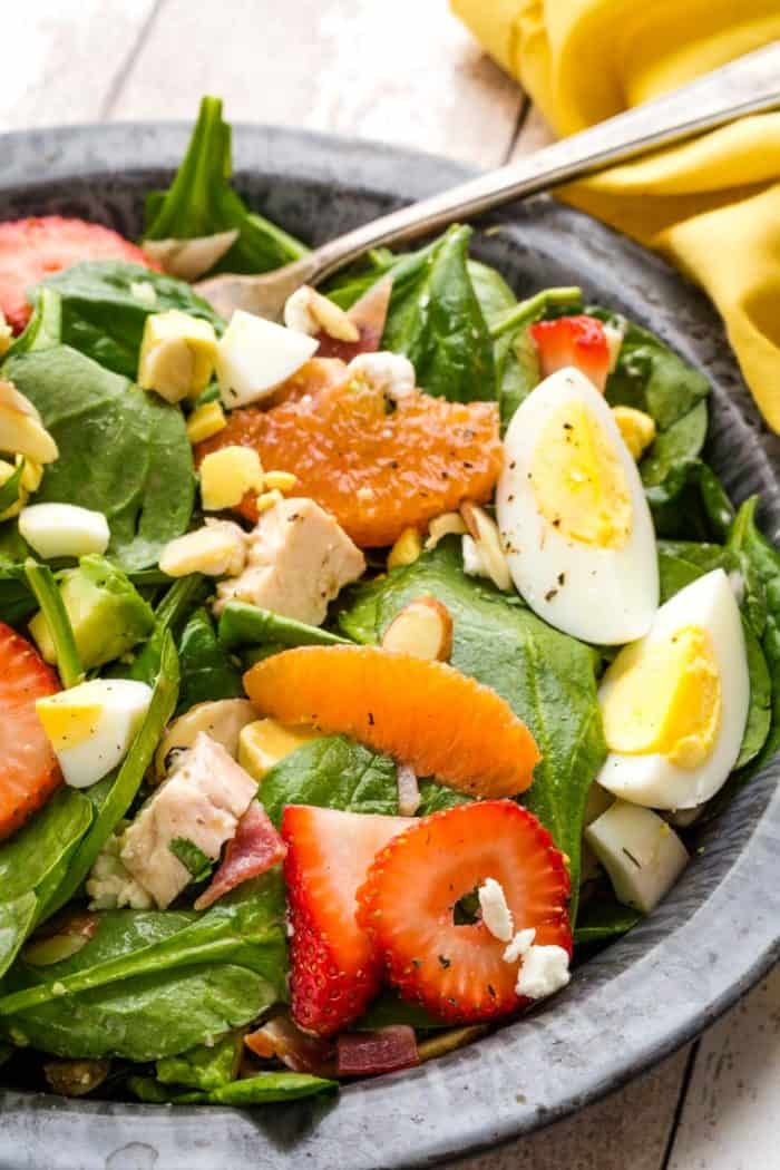 Tossed strawberry spinach salad with poppyseed dressing, plus chicken, avocado, eggs, goat cheese, and bacon