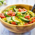 A wooden serving bowl with Sauteed Zucchini, Squash, Tomatoes, and Corn in Brown Butter
