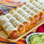 Cheesy Baked Hot Dog Taquitos served with guacamole and salsa
