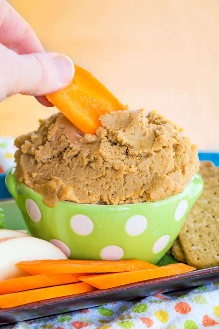 Dipping a carrot in Sweet Peanut Butter Hummus