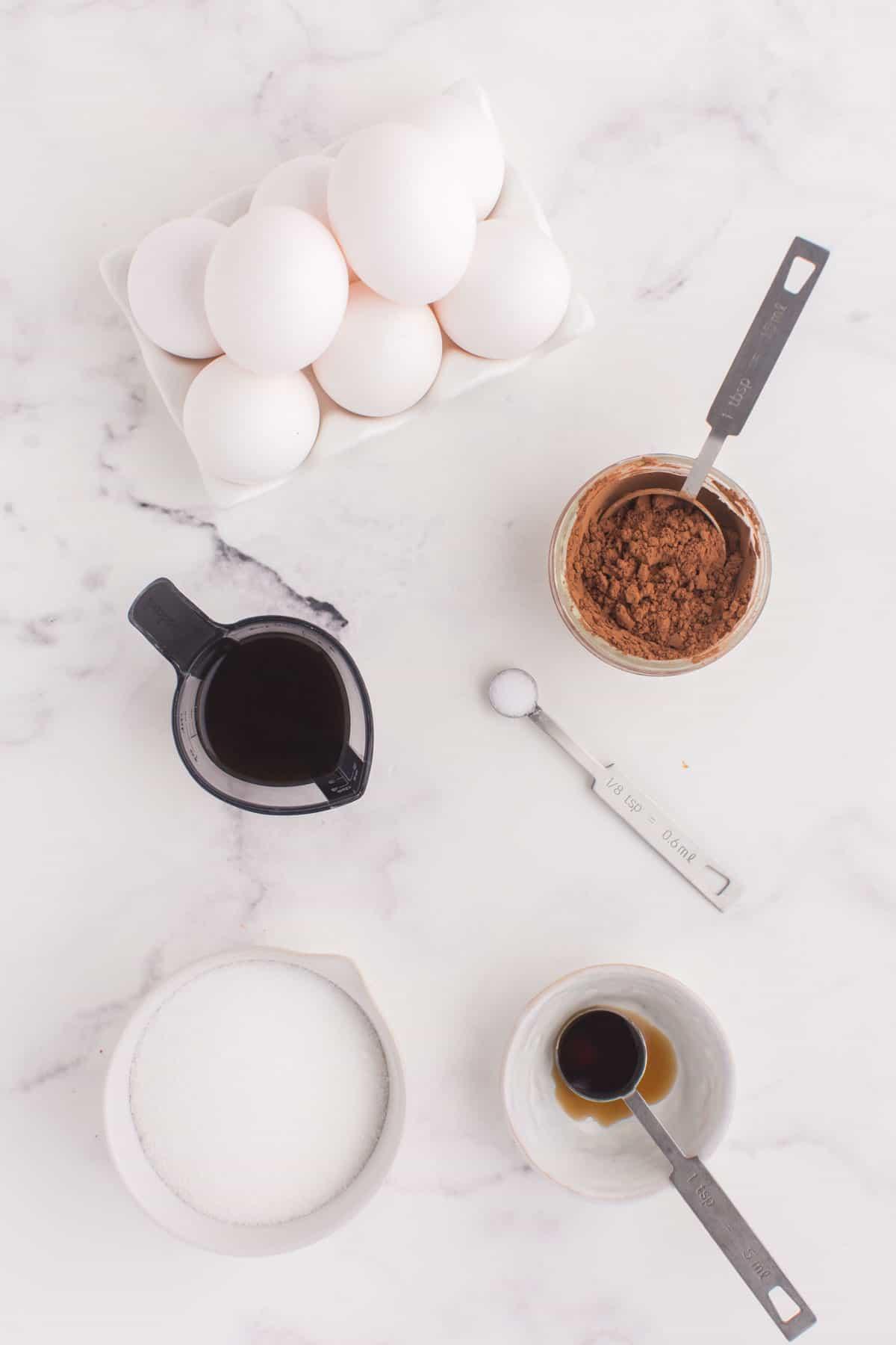 Eggs, cocoa powder and sugar in bowls