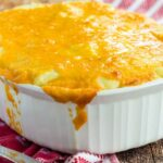 A white baking dish with Low Carb Shepherd's Pie and cheese on top and down the sides