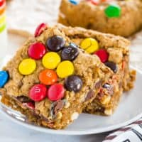 A stack of two No Flour Monster Cookie Bars on a small white plate