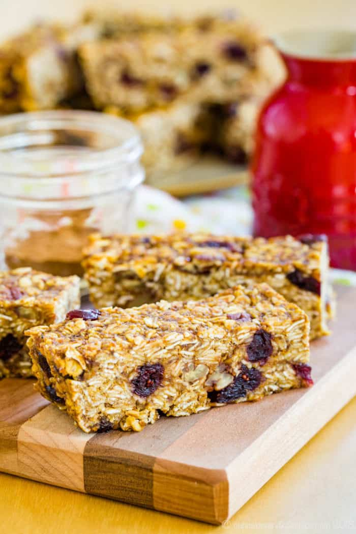A pumpkin granola bar with cranberries and nuts on a cutting board