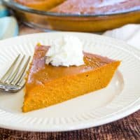 A piece of no crust pumpkin pie with whipped cream on a plate
