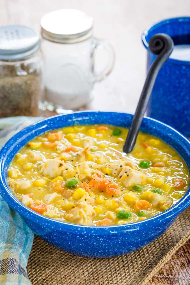 A blue bowl of Chicken and Corn Chowder with a soup spoon