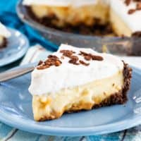 Dulce de Leche Banana Cream Pie slice on a plate with whole pie in background