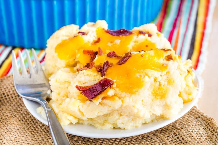 A scoop of Low Carb Cauliflower Mashed Potatoes with cheddar cheese and bacon on a plate