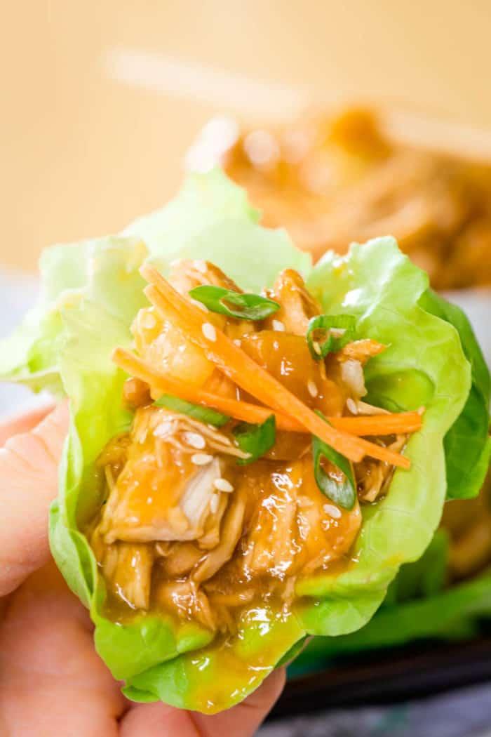 Hand holding a Teriyaki Chicken Lettuce Wrap
