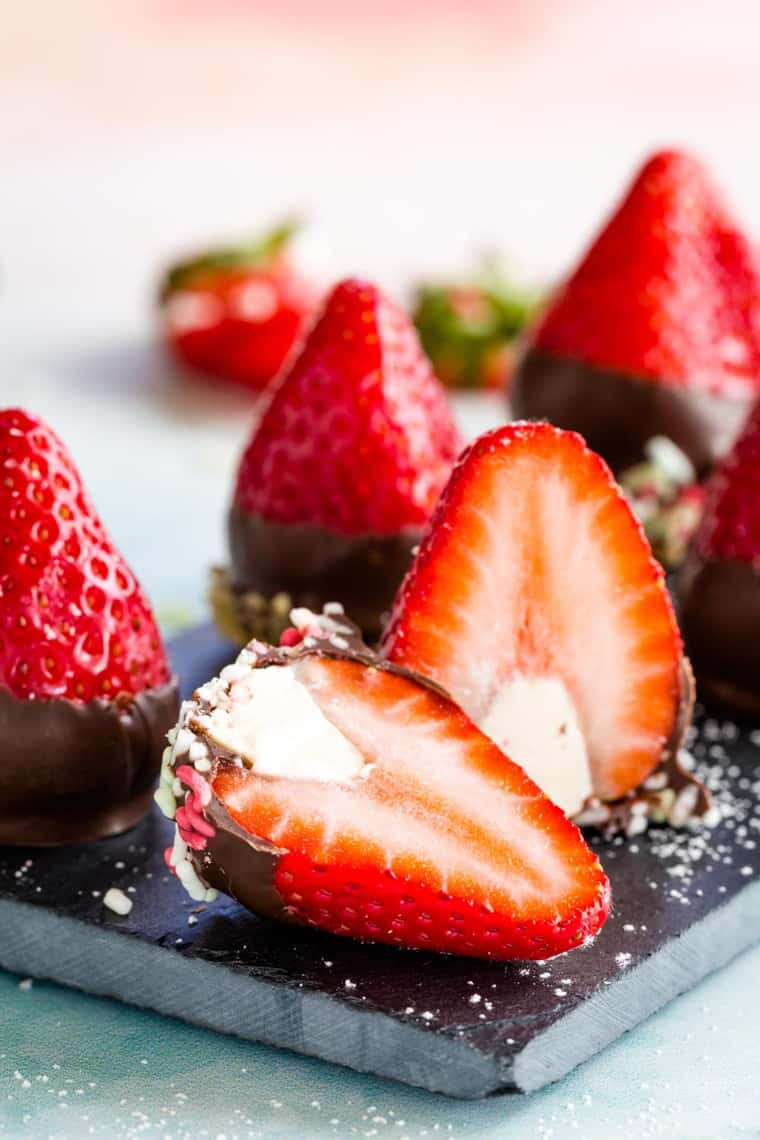 One of the cut open cheesecake stuffed strawberries dipped in chocolate