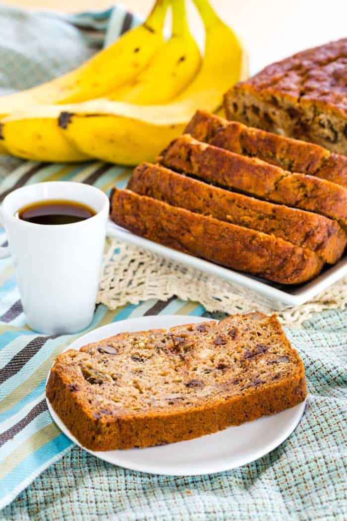 A piece of gluten free banana bread with a cup of coffee