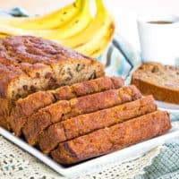 Gluten Free Banana Bread on a white platter with a slice on a plate