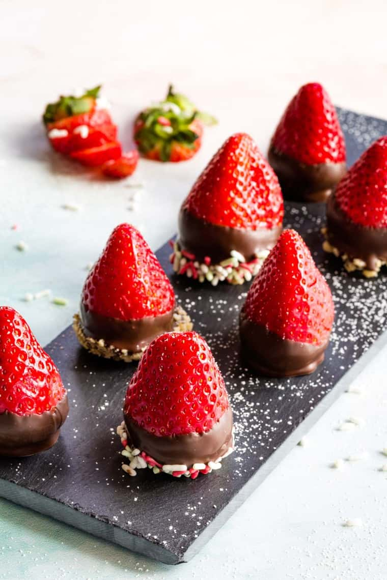 Chocolate Covered Cheesecake Stuffed Strawberries on a slate platter with powdered sugar
