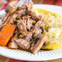 A plate of crockpot balsamic beef pot roast with mushrooms, carrots and peas over polenta