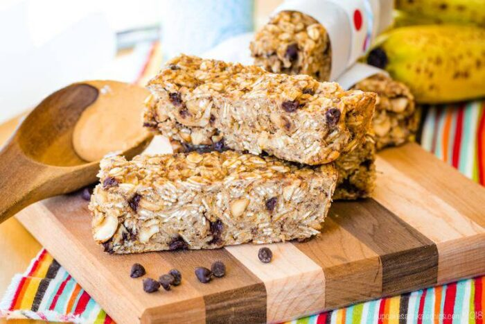 Banana Chocolate Chip Peanut Butter Granola Bars stacked on a cutting board