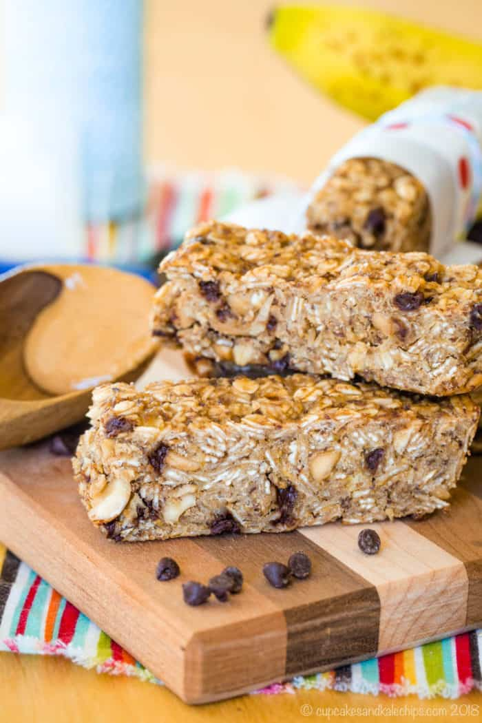 Banana Granola Bars with chocolate chips and a spoon of peanut butter on a cutting board