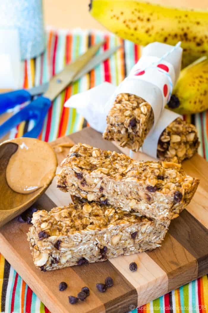 Overhead of Banana Peanut Butter Chocolate Chip Granola Bars with supplies for wrapping them in parchment paper