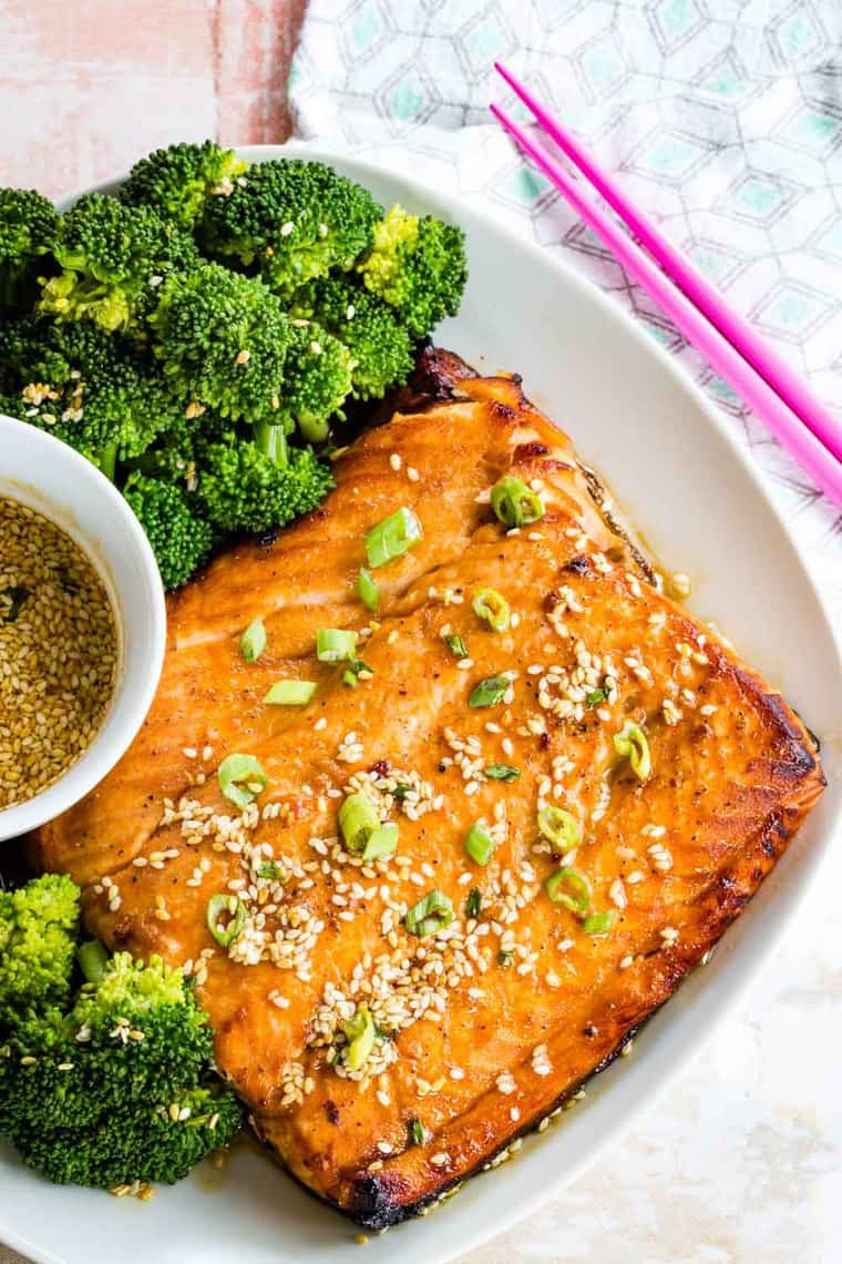 Maple Sesame Salmon and broccoli on a plate with pink chopsticks