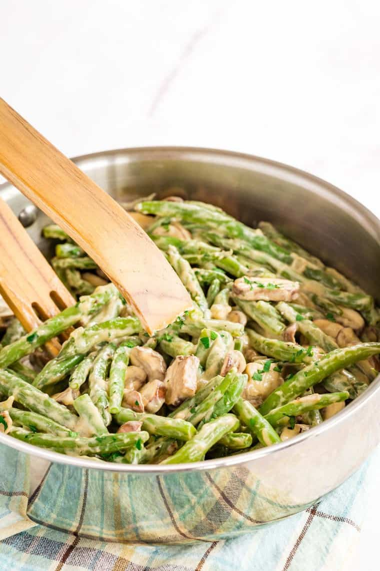 Creamy Green Beans and Mushrooms with wooden tongs in a skillet