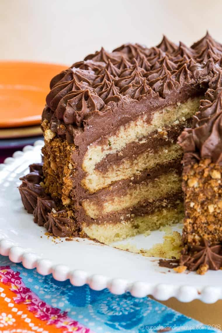 Looking into a sliced gluten free yellow butter cake to see layers of cake and chocolate frosting