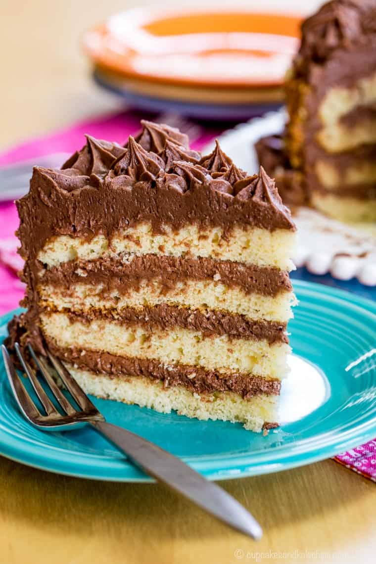 A slice of gluten free layer cake with chocolate buttercream