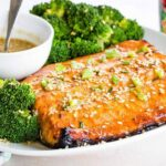 Sesame Maple Glazed Salmon serves on a plate with broccoli and sauce