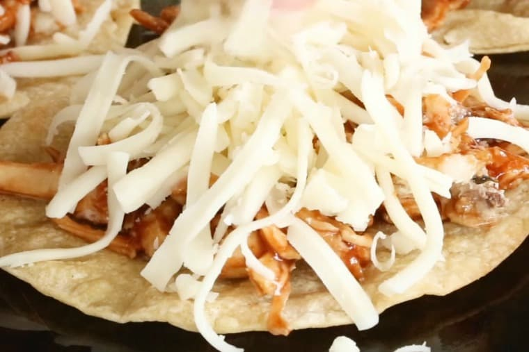 Add shredded cheese on top of barbecue chicken tostadas