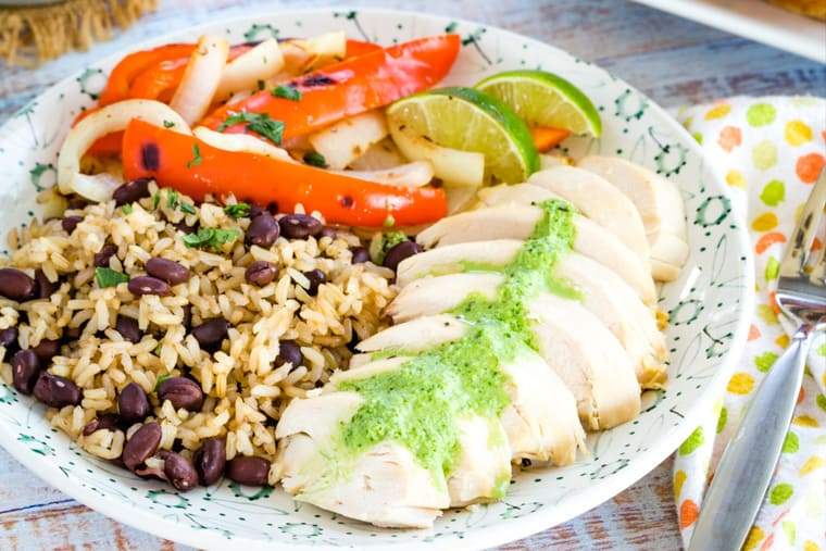 Plate of chicken with green sauce, rice and beans, and vegetables
