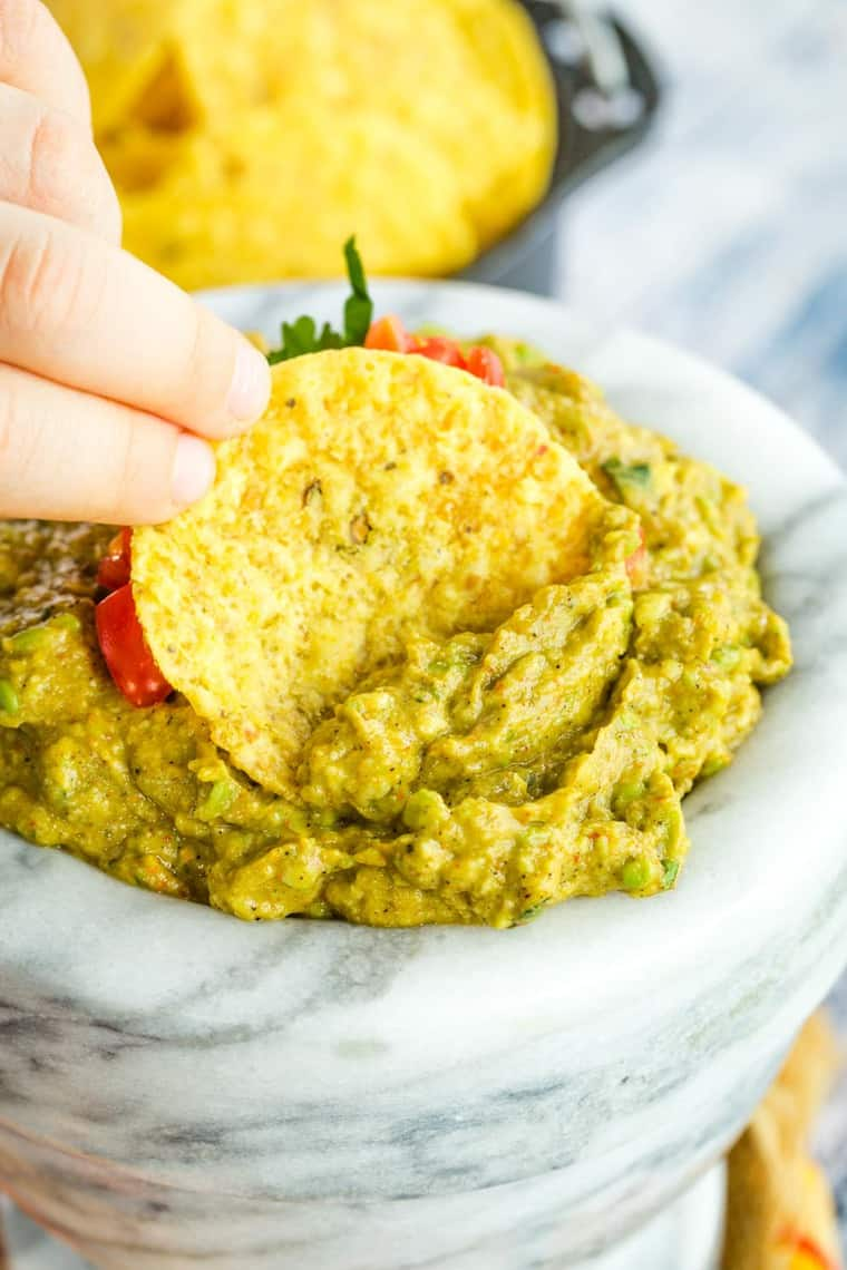Kids fingers holding a chip to scoop guacamole