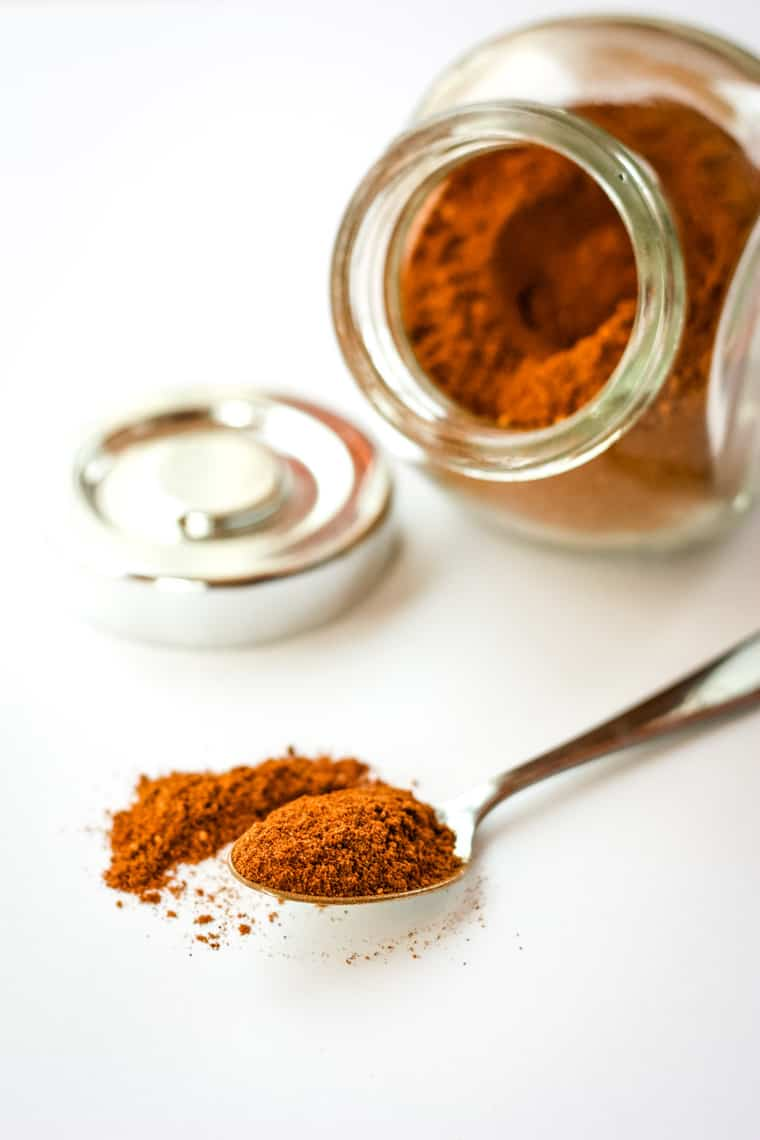 Mexican Chocolate Spices on a spoon with a jar in the background