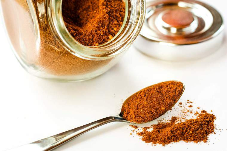 A spoon spilling over with the spice mix of cinnamon, ginger, and cayenne pepper