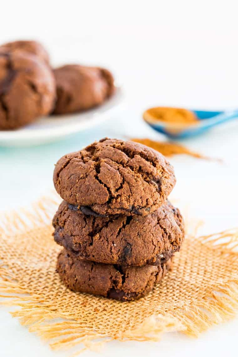 A stack of three Flourless Mexican Hot Chocolate Cookies with a spoon of Mexican Chocolate Spice Mix in the background