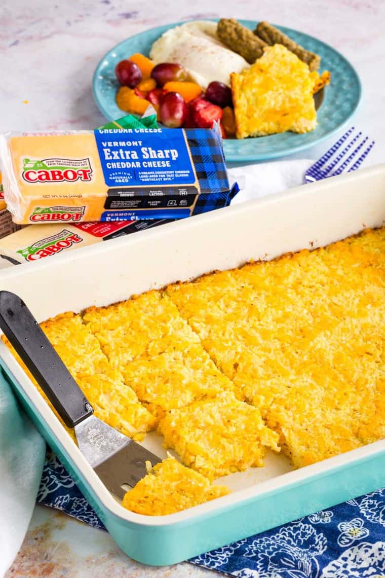 Cheesy Cauliflower Hash Browns Casserole in a baking dish with packages of Cabot cheddar cheese
