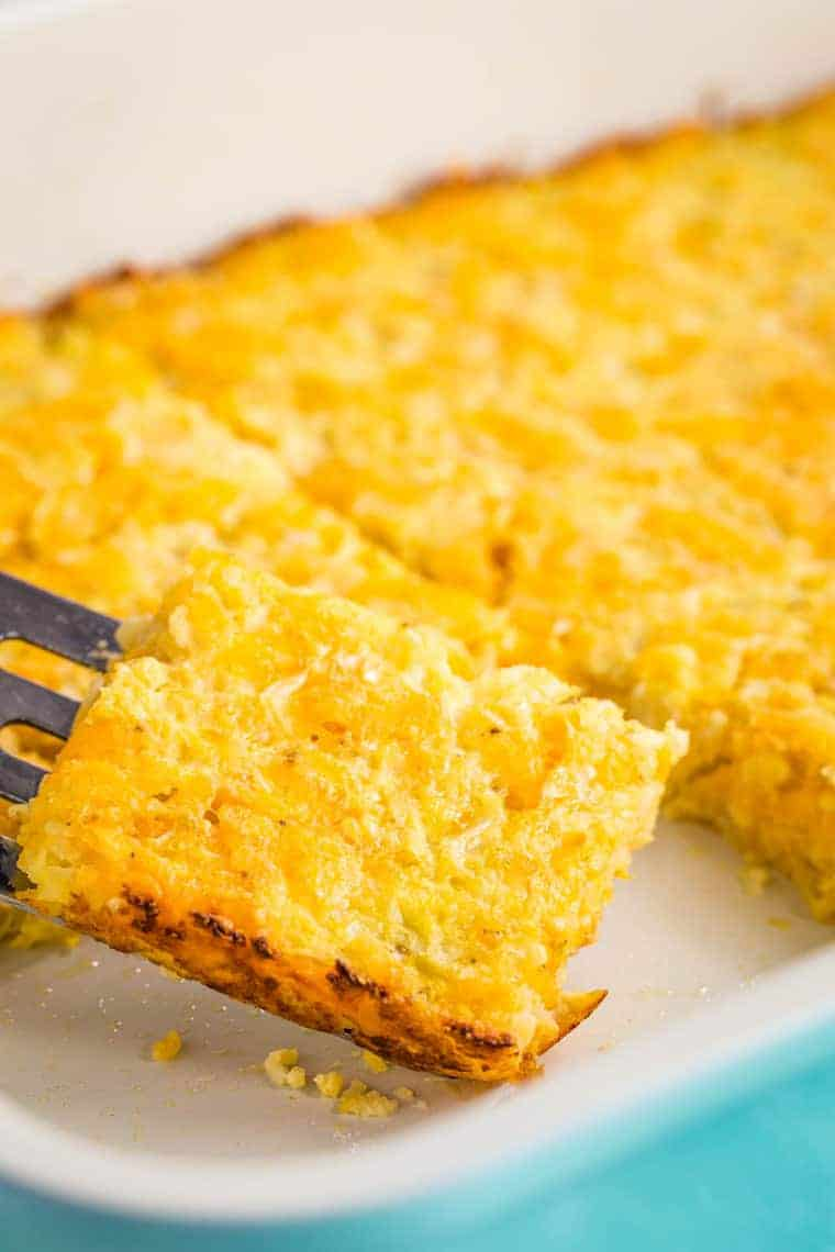 A piece of Cauliflower Hash Brown Casserole being picked up ona spatula from the baking pan