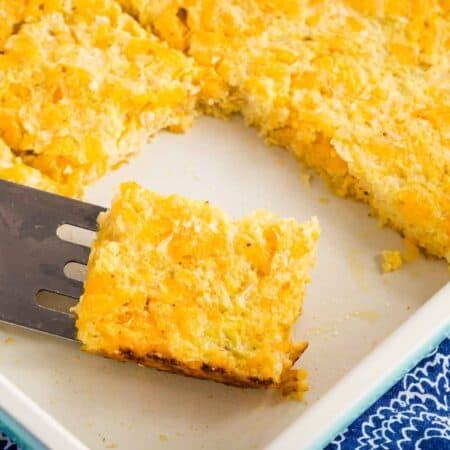 A piece of Cheesy Cauliflower hash Browns Casserole on a spatula in a baking dish